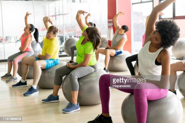 group of diverse people at the gym stretching while sitting on exercise balls - aerobics stock pictures, royalty-free photos & images