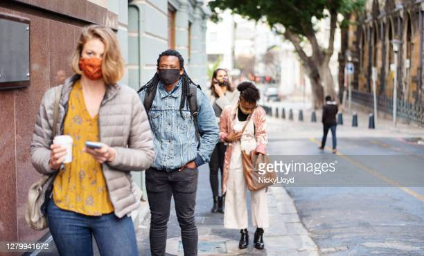 group of diverse people in face masks social distancing on a city sidewalk - waiting in line stock pictures, royalty-free photos & images
