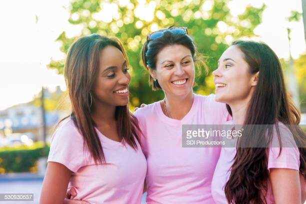 Group of diverse women in pink breast cancer awareness shirts