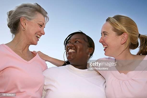 Grupo de diversas mulheres sorrindo para os outros