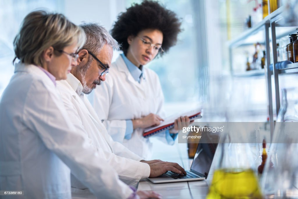 Group of doctors analyzing medical data on laptop in the laboratory. : Stock Photo