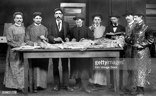 A group of doctors in training in the late 19th century examine a dissected human body laid out on a wooden table
