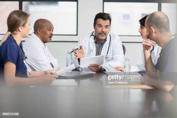 group of doctors sitting at table, having discussion - group of doctors stock pictures, royalty-free photos & images