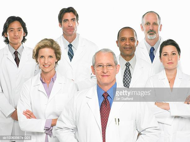 Group of doctors standing on white background, portrait