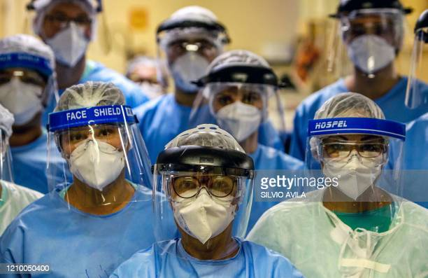 Group of doctors working with patients infected with the novel coronavirus COVID-19 wear face shields at the Intensive Care Unit of the Hospital de...