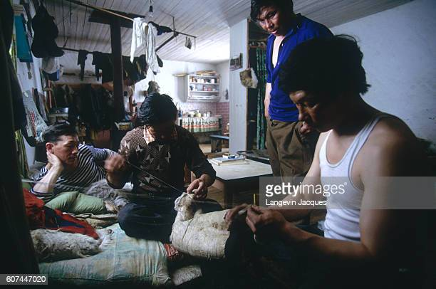 A group of Dolgan men sew clothing from animal skins in their home near the village of Syndassko Russia The Dolgans traditionally a nomadic people...
