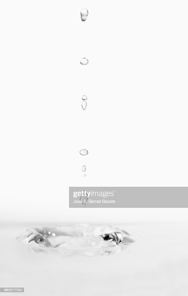 Group of drops on line suspended in the air, falling down on a water surface that forms figures and abstract forms, on a white background : Stock Photo