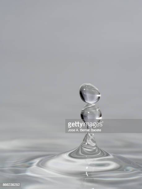 group of drops on line suspended in the air, falling down on a water surface that forms figures and abstract forms, on a gray background - petit groupe d'objets photos et images de collection