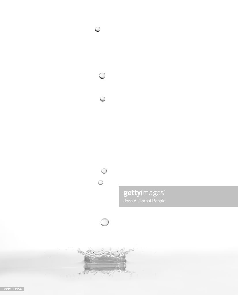 Group of drops on line suspended in the air, falling down on a water surface that forms figures and abstract forms, on a gray background : Stock Photo
