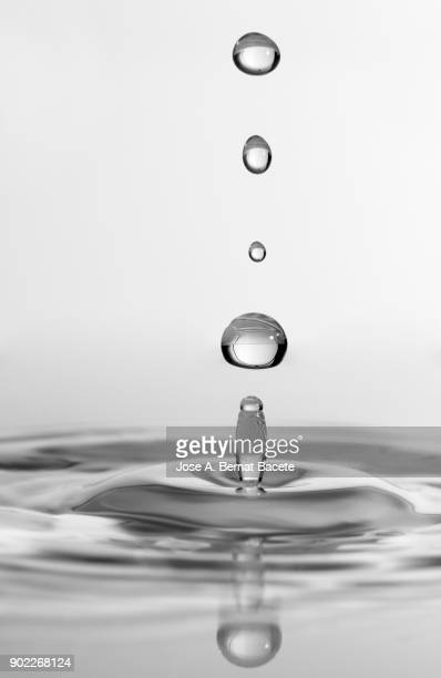 group of drops on line suspended in the air, falling down on a water surface that forms figures and abstract forms, on a gray background - drop stock photos and pictures