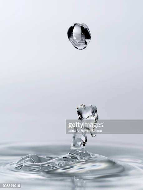 group of drops on line suspended in the air, falling down on a water surface that forms figures and abstract forms, on a white background. - petit groupe d'objets photos et images de collection