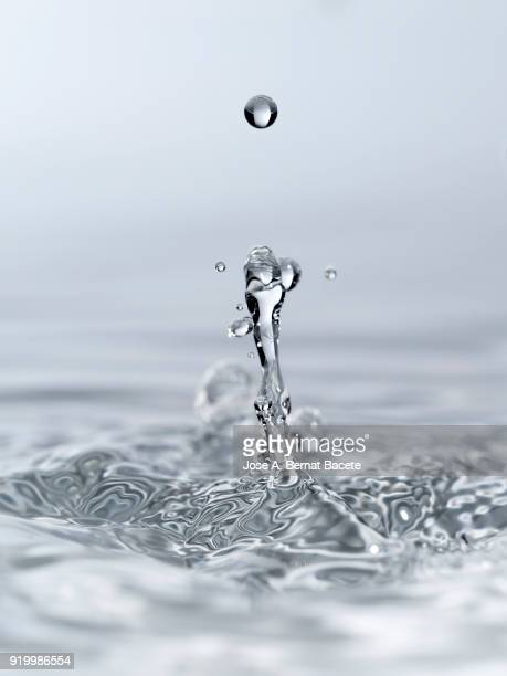 Group of drops on line suspended in the air, falling down on a water surface that forms figures and abstract forms, on a white background.