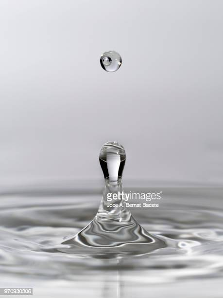 group of drops on line suspended in the air, falling down on a water surface that forms figures and abstract forms, on a white background. - falling water stock photos and pictures