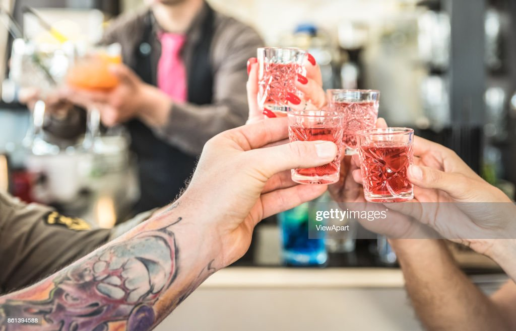 Group of drunk friends toasting cocktails at bar restautant - Food and beverage concept on nightlife moments - Defocused bartender serving drinks on background - Focus on hands cheering red shot glass : Stock Photo