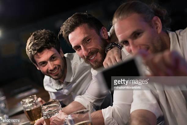 Group of drunk men taking selfies