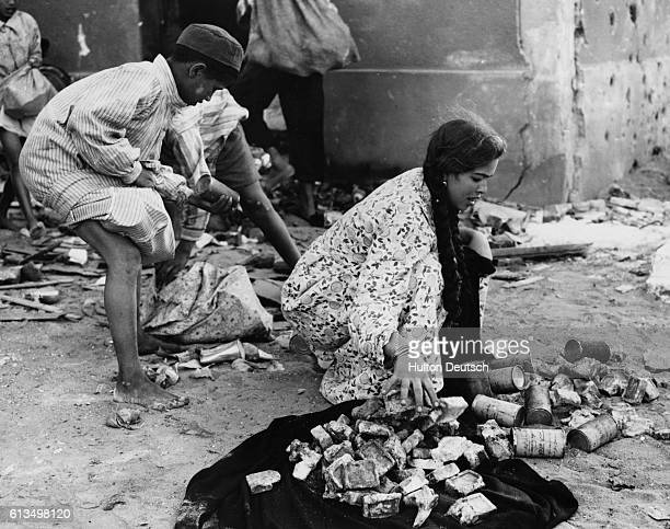 A group of Egyptian children grab cans of food after looting a food dump during the Suez Crisis of 1956
