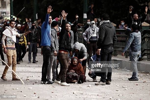 A group of Egyptian protesters gesture to other demonstrators to stop throwing rocks to protect an old women sitting on the ground between two...