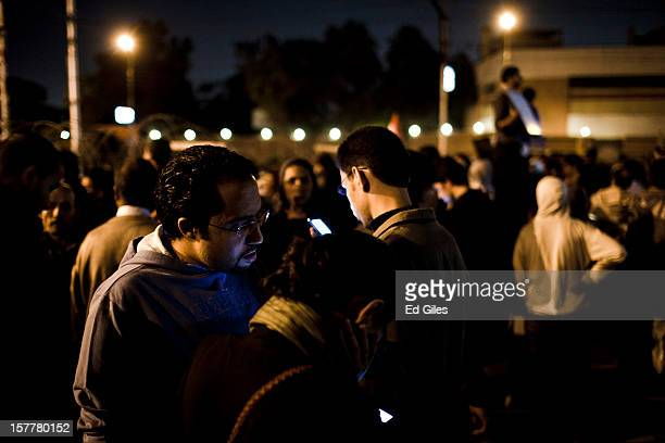 A group of Egyptian protesters look at mobile phones during a demonstration in front of Egypt's Presidential Palace after violent clashes the...