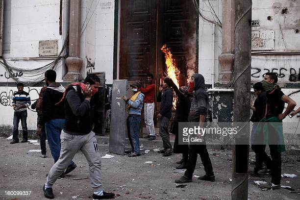 A group of Egyptian protesters stand in front of a burning school building during a protest following the announcement of the death penalty for 21...