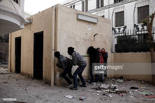A group of Egyptian protesters take cover from nearby Egyptian riot police during a protest following the announcement of the death penalty for 21...