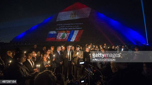 Group of Egyptian tourism guides hold candles in front of the great pyramid of Khufu as French flag lighted on it in Giza, outskirt of Cairo on...