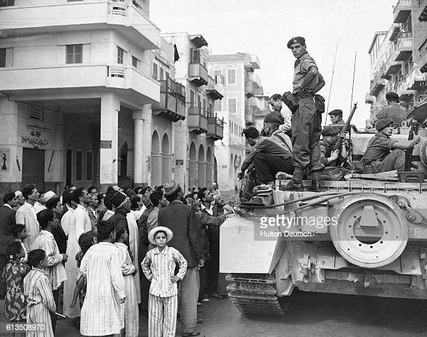 A group of Egyptians crowd around a British tank during the Suez Crisis of 1956
