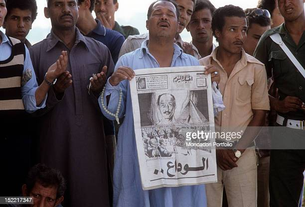 A group of Egyptians is praying at Sadat funerals a man shows a newspaper with Sadat photos Medinet Nars