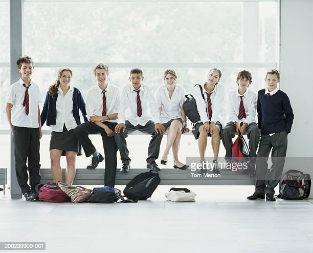 Group of eight schoolchildren (12-16) relaxing by window, smiling