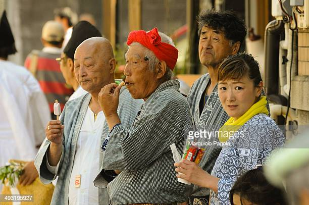 Group of elder people is talking and laughing in a local religios celebration at Kamakura, Kanagawa Prefecture, Japan.
