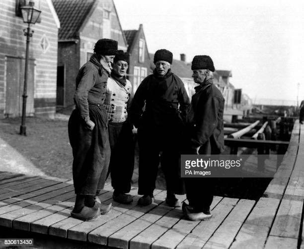 A group of elderly Dutchmen wearing their traditional dress including clogs at the port of Marken in the Netherlands