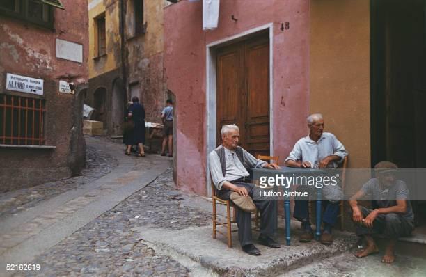 A group of elderly men outside a cafe in Portofino Italy circa 1970