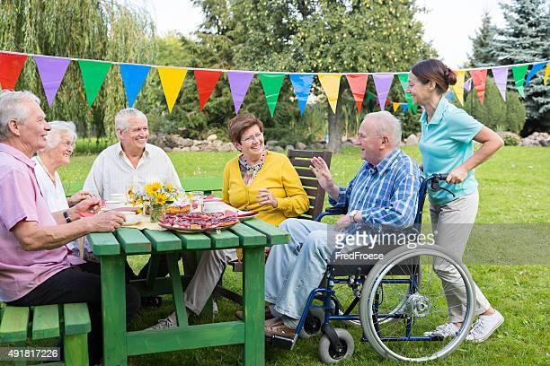 Groupe de personnes âgées assis à la table de jardin