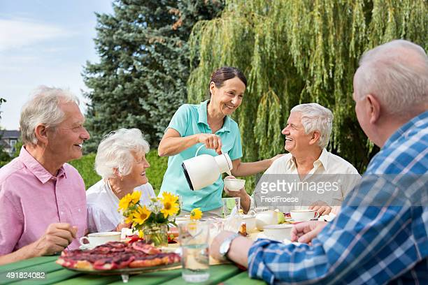 Group of elderly people sitting at the garden table