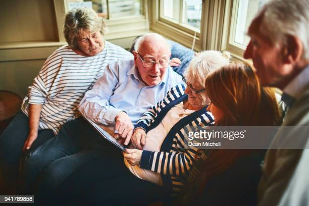 group of elderly people with young woman using digital tablet - hospice stock pictures, royalty-free photos & images