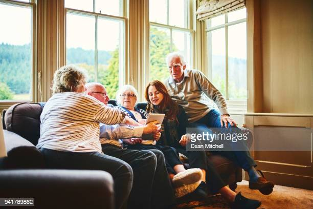 Group of elderly people with young woman using digital tablet