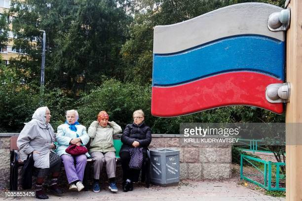 A group of elderly women speak together as they sit on a bench next to a wooden Russian national flag on September 15 in the suburb of...