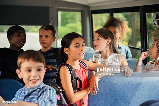Group of elementary age kids in a school bus.