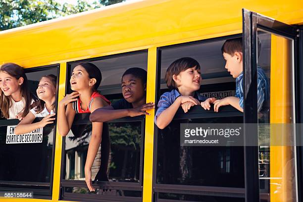 Group of elementary age kids on a yellow school bus.