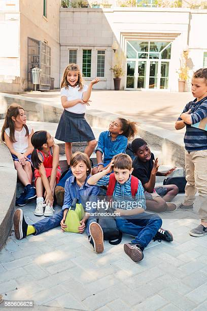 Group of elementary age kids posing in front of school.