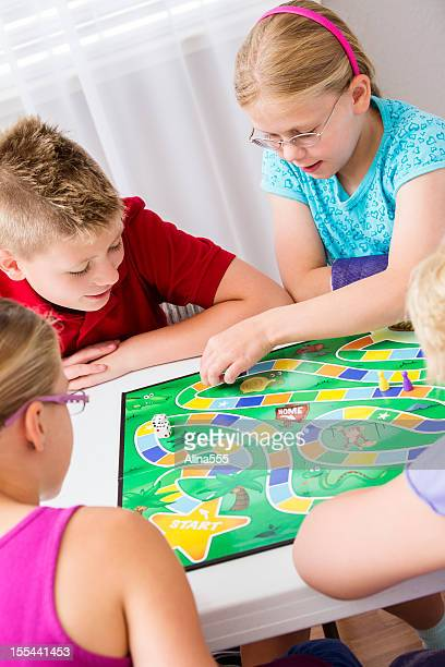 group of elementary kids playing a board game - game board stock photos and pictures