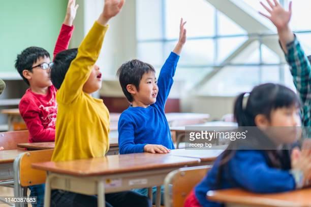 教室で手を上げている小学生たちのグループ - 公共の建物 ストックフォトと画像