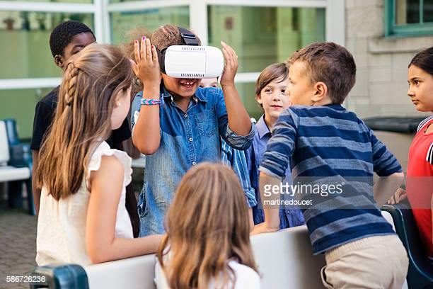 Group of elementary school kids experiencing virtual reality glasses.