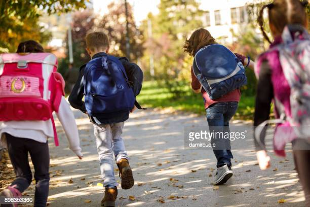 group of elementary school pupils running outside - educazione foto e immagini stock