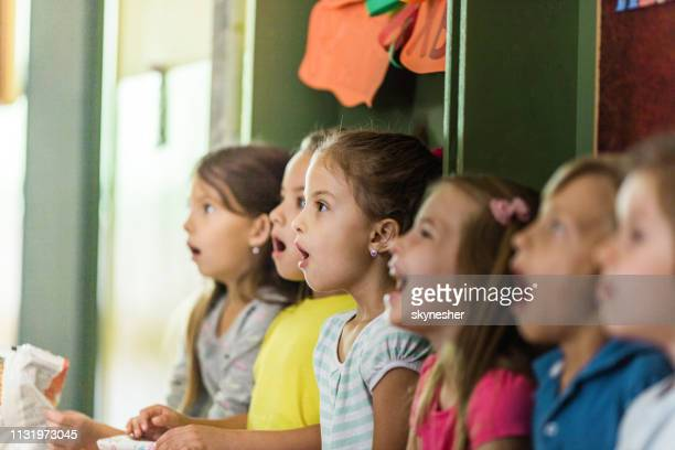 group of elementary students singing in choir at school. - cantare foto e immagini stock