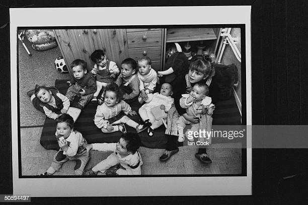 Group of eleven Bosnian war orphans sitting on mattress on floor in group home; the orphans were part of the 44 children who were driven through...