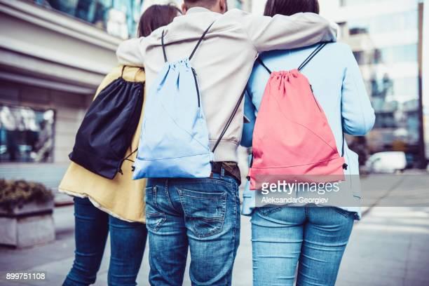 Umarmt Studentengruppe mit Rucksäcken zu Fuß nach der Schule