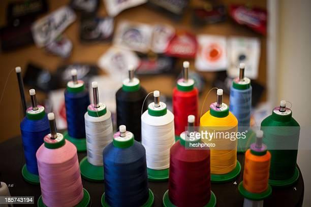 group of embroidery thread bobbins on machine - heshphoto stock-fotos und bilder