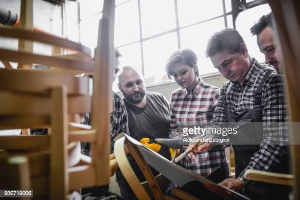 Group of Engineers Looking at Blueprint Plans in Their Workshop