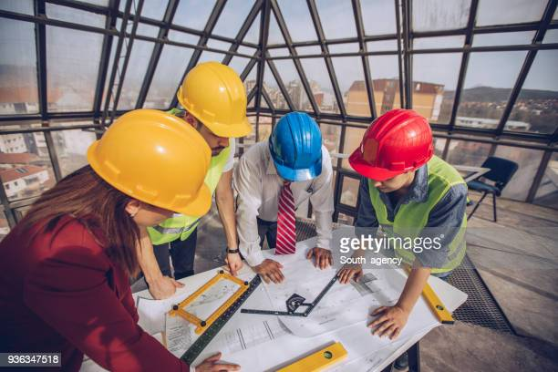Group of engineers looking at blueprints at construction site