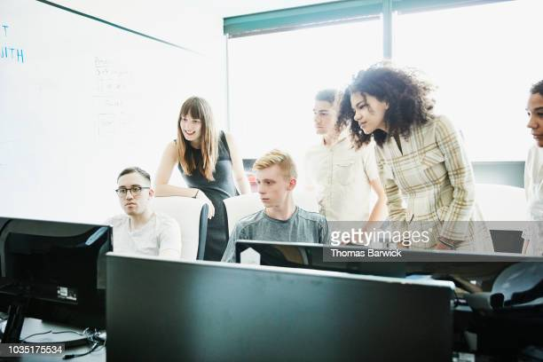 group of engineers working together on coding problem in computer lab - digital native stock pictures, royalty-free photos & images